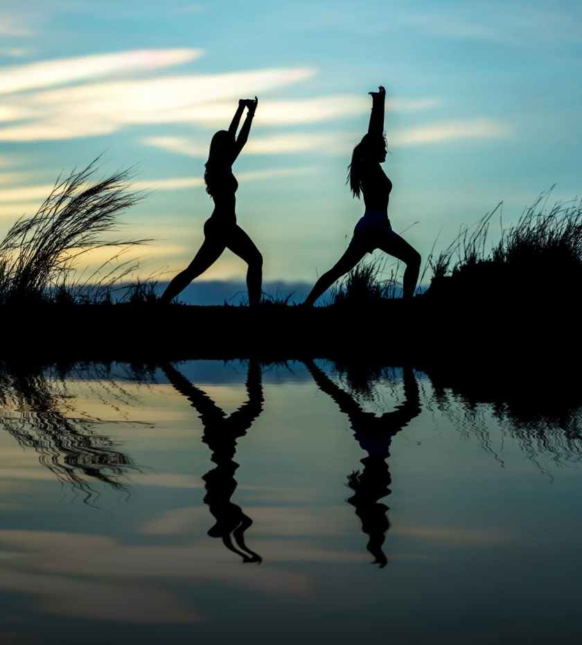 silhouette of women on lake against sky